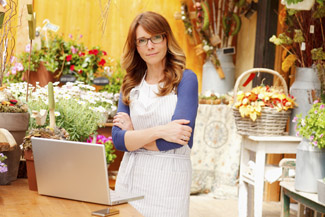 Image of business woman at her shop with her laptop
