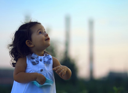 Little, young girl looking to the sky with power lines in the background.