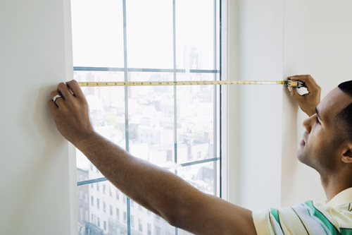 A man measuring a window with a tape measure.