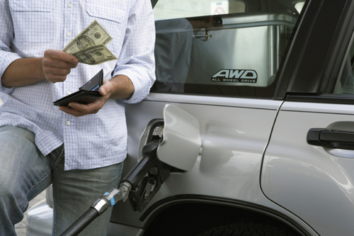 Man pumping gas into his car with cash in his hand.