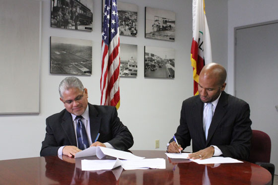 U.S. Department of Labor Regional Administrator for the Western Region Ruben Rosalez and California Department of Justice General Counsel Brian Nelson sign the memorandum of understanding.