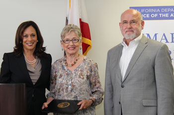 AG Harris presents Suzy McCausland and Tom Gammon with a Smart on Crime Award.